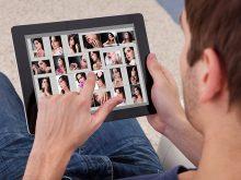 タブレットで女性写真を見る男性